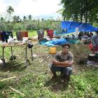 Kilisi Tuiuli (28) sits in front of his family's makeshift home high in the hills above...