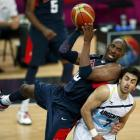 Kobe Bryant (left), of the US, looks to make a pass while resting on the back of Argentina's...
