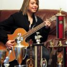 Dunedin musician Kylie Price (14) strums her six-stringed pride and joy and surveys her trophies....
