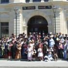 Ladies and gents attired in Victorian garb gathered on the steps of the opera house at midday...