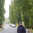 Lawrence community board member Brent Taylor with the Lombardy poplars that line State Highway 8...