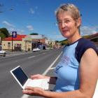 Lawrence woman Nina Arron prepares to use her laptop in the main street of Lawrence. Photo by...