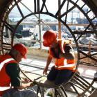 Lawrie Forbes (right) and Alan Bryan, of Zeal Steel, start to remove one of four cast-iron clock...