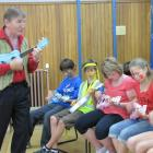 Learning a few chords from Australian music teacher Mike Jackson are Queenstown Primary School...