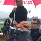 Liam (4) and Craig Direen, of North Otago, and Lisa Direen (Christchurch) keep dry during several...