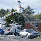 Live, dangling power lines posed an extreme danger to the driver of this car after it toppled a...