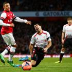 Liverpool's Luis Suarez reacts to a challenge in the penalty area from Arsenal's Alex Oxlade...