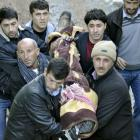 Locals carry a victim killed in air strikes to the morgue of a hospital in Uludere, of the Sirnak...