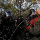 Macedonian police officers stop stranded migrants in a forest, as they try to cross the Greek...