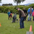 Malcolm Hancox prepares to  swing on the novelty golf course at the West Otago Health Centre's...
