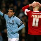 Manchester City's Carlos Tevez (L) celebrates after scoring his third goal against Barnsley...