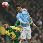 Manchester City's David Silva (R) vies for the ball with Norwich City's Nathan Redmond. Photo:...