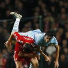 Manchester City's Stefan Savic (R) challenges Liverpool's Andy Carroll during their League Cup...