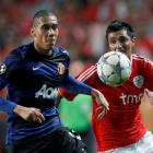 Manchester United's Chris Smalling (L) and Benfica's Oscar Cardozo fight for the ball during...