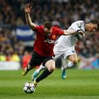 Manchester United's Phil Jones (L) challenges Real Madrid's Mesut Ozil during their Champions...