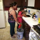 Marisela Corona, 26, (L) whose well has run dry, washes dishes with her daughter Andrea Andrade...