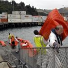 Mark Tully, of the Otago Regional Council, leads a team of people carrying a land sea boom used...