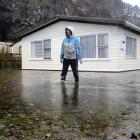 Mary Allison checks on her next door neighbour's property after heavy rainfall at Long Beach on...