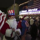 Matt Ornstein, dressed in a Santa Claus costume, holds an American flag as fans line up at the...