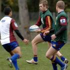 Matt Saunders (middle) looks to move the ball on to Kendrick Lynn at training at Logan Park...