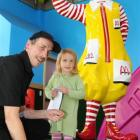 McDonald's employee Alan Garthwaite is in his element as he hands a toy to Evie O'Dowda (2)....