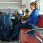 Melissa Giddens (18) waits for her flight out of Dunedin to Wellington after a raft of flights...