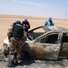 Members from the UN observers mission inspect a burnt car near Deir al-Zour city, northeastern...
