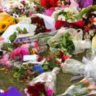 Flowers are laid out under a tree at Cathedral Square