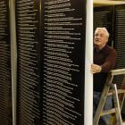 Otago Settlers Museum preparator Steve Munro helps prepare banners for an honour roll display....