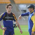 Michael Hobbs listens to some advice from Highlanders head coach Glenn Moore at Carisbrook...