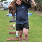 Michael Marshall, of West Otago, carries the carcass of a wild pig in the obstacle course section...