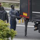Migrants climb into the trailer of a truck during an attempt to make a clandestine crossing to...