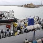 "Migrants sit on the ""Fiorillo"" Coast Guard vessel as they arrive at the Porto Empedocle harbour...."