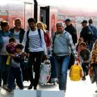 Migrants walk beside a train after arriving at the main railway station in Munich, Germany....