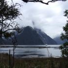 Mitre Peak hides its face behind a veil of cloud as a tourist vessel returns from an excursion on...