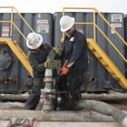 Mody Torres (left) and Josh Anderson connect hoses between a pipeline and water tanks at a Hess...