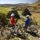 Mountain bikers take in the view from what will be part of the  Around the Mountains Cycle Trail....