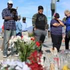 Mourners gather around a makeshift memorial in honor of victims following their attack in San...