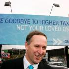 National Party leader John Key stands in front of National's new billboard campaign in Auckland....