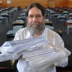NCEA exam supervisor Neil Copeland with answer booklets collected after the level 2 biology exam...