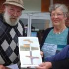 Neil and Margaret Roy, of Macraes, hold a photo showing one of the incorrect signs displayed...