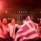 New Democracy supporters hold flares as they celebrate in front of the parliament in central...