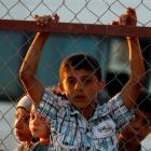 New Syrian refugee children look out from behind a fence as they arrive at a stopover facility...