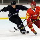 New Zealand's Andrew Cox (left) and China's Tianyu Hu compete for the ball during their ice...
