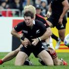 New Zealand's Colin Slade (C) drops the ball as he is tackled by Canada's Phil Mackenzie during...