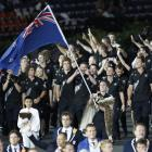 New Zealand's flag bearer Nick Willis holds the national flag as he leads the contingent in the...