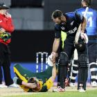 New Zealand's Grant Elliot (R) helps South Africa's bowler Dale Steyn up after New Zealand won...