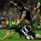 New Zealand's Simon Mannering, right, and Adam Blair, top, tackle Australia's Brent Tate during...