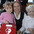 """Nicci Reddy with daughters Caitlin (left) and Madison Frost with the """"Heartstart"""" defibrillator..."""