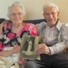 Noeline and Jim Wilson with their wedding photo and Mrs Wilson's wedding dress at their Oamaru...